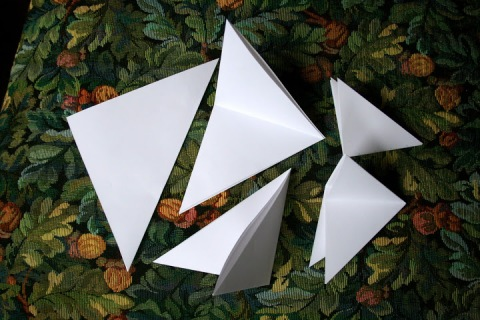 Fold each square in half to make a triangle.  Then fold in half again.  And again.