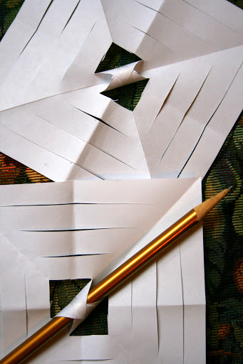 Starting with the smalled inner square, fold two points together and tape.