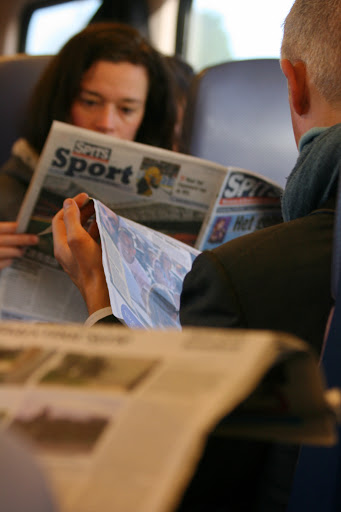 Commuters reading the newspaper on the train