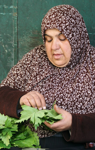 Arab women sorting grape leaves in the market
