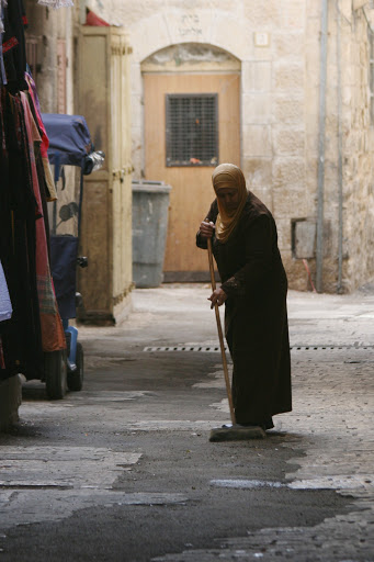 In the souk, a vendor sweeping in front of her stall
