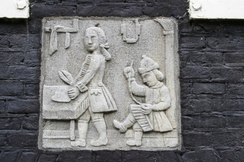 Plaque on one house showing tailors at work