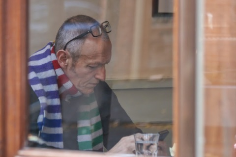 Man in a striped scarf in coffee shop