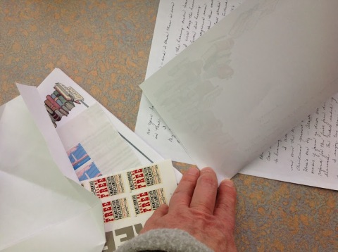 First find the exact center of the long side of your stationery and make a small crimp to mark the spot.