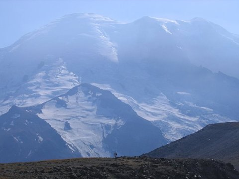 Hiker dwarfed by Mount Rainier