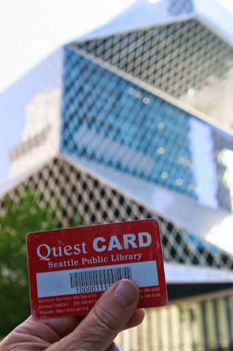 My library card, held up outside the Central Library in downtown Seattle
