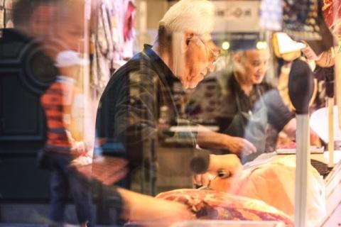 Busy slicing ham, through a shop window