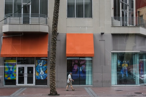 Pedestrian on Canal Street passing images of the ubiquitous blue dog (art by George Rodrigue)